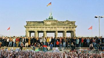 Am 9. November 1989 öffnet die DDR ihre Grenze nach Westberlin und zur Bundesrepublik; nach 28 Jahren fällt die Mauer. Bewohner aus West- und Ostberlin stehen auf der Mauerkrone am Brandenburger Tor.